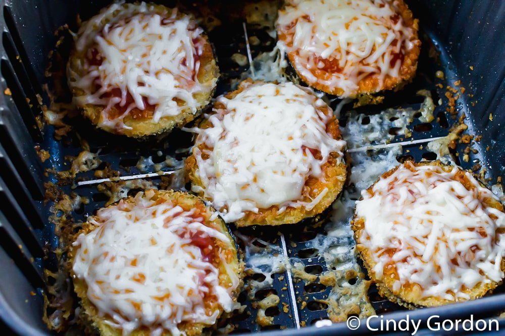 eggplant parmesan slices topped with sauce and cheese in an air fryer basket.