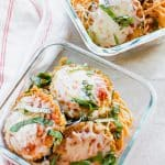 glass dishes filled with spaghetti and eggplant parmesan.