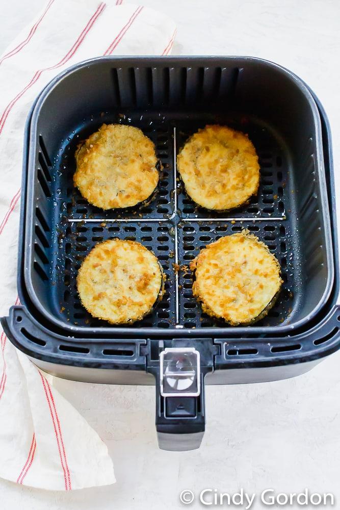 Crispy eggplant slices in an air fryer basket.