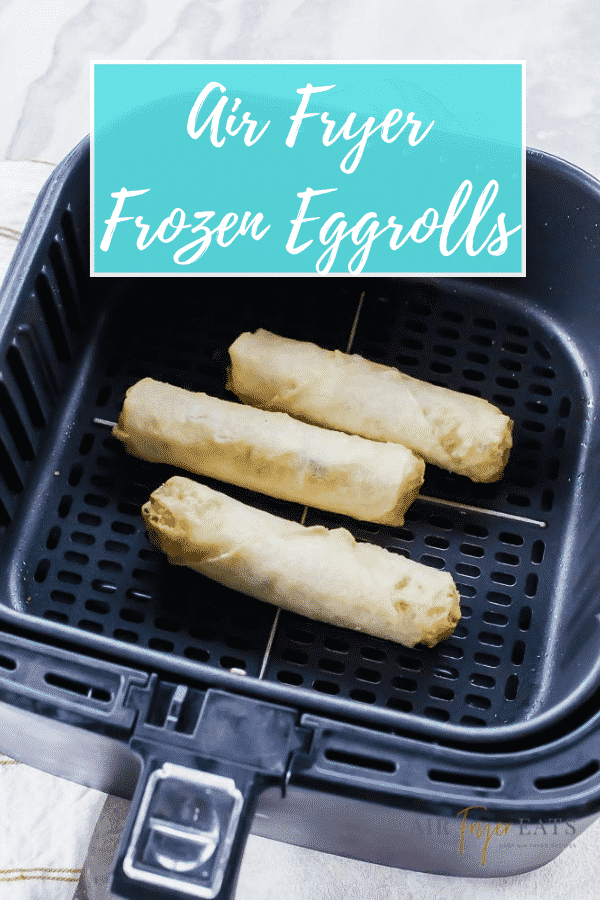 three egg rolls in black air fryer basket with text over lay saying air fryer frozen eggrolls
