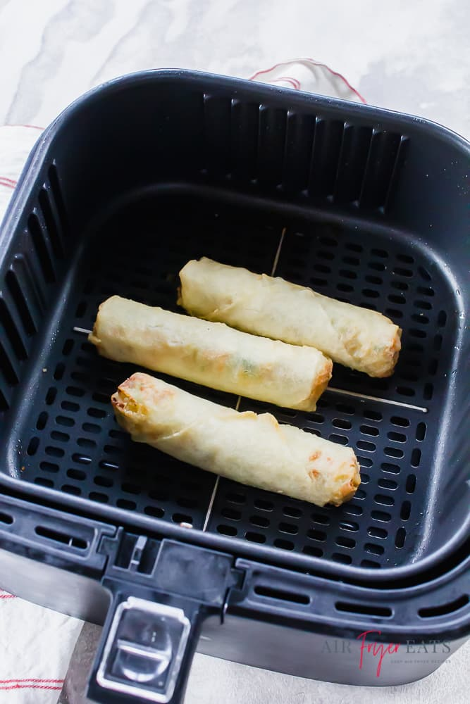 A square air fryer basket with three eggrolls in it.