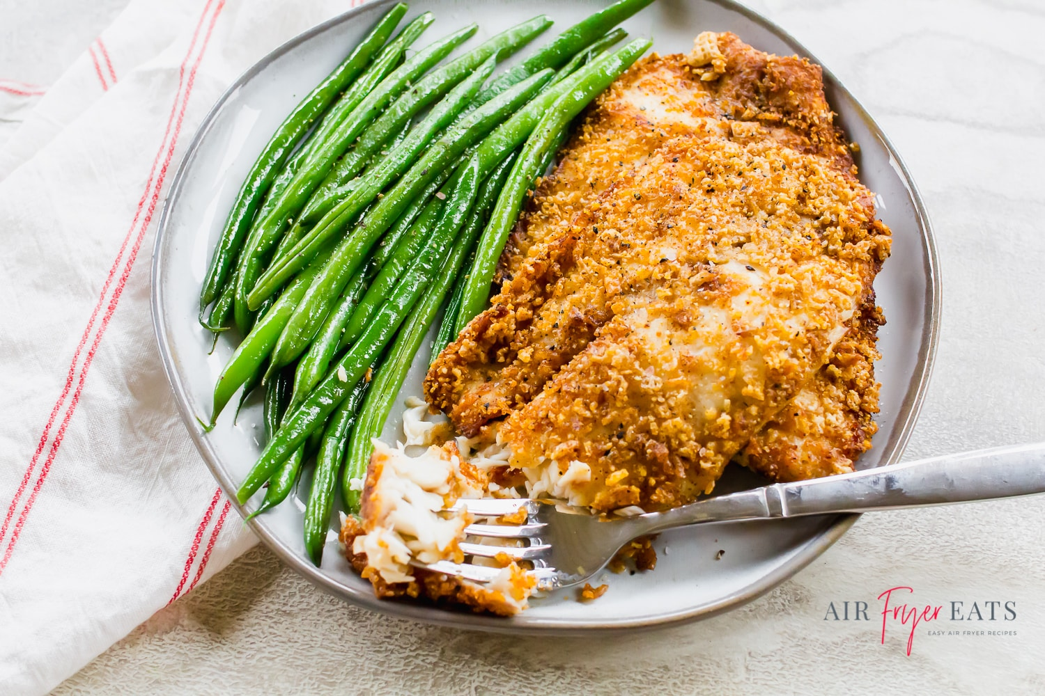 Flaky air fryer tilapia with green beans on a round gray plate with a fork