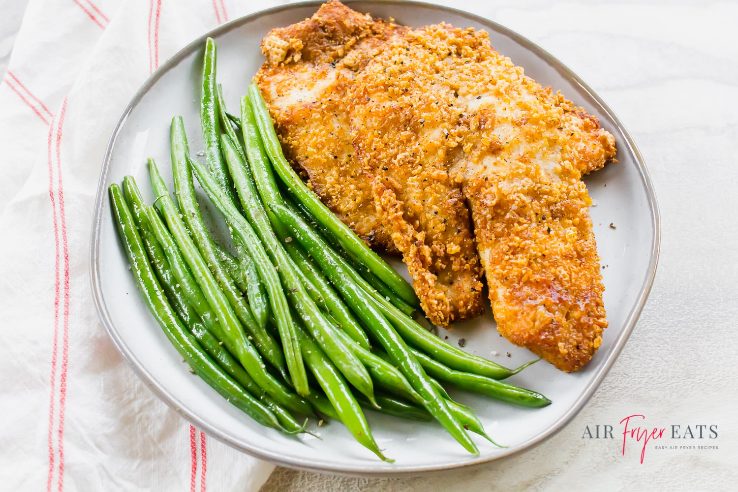 Overhead shot of air fryer tilapia on a gray plate with sautéed green beans