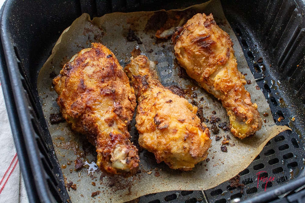 3 fried chicken drumsticks on parchment paper in an air fryer basket