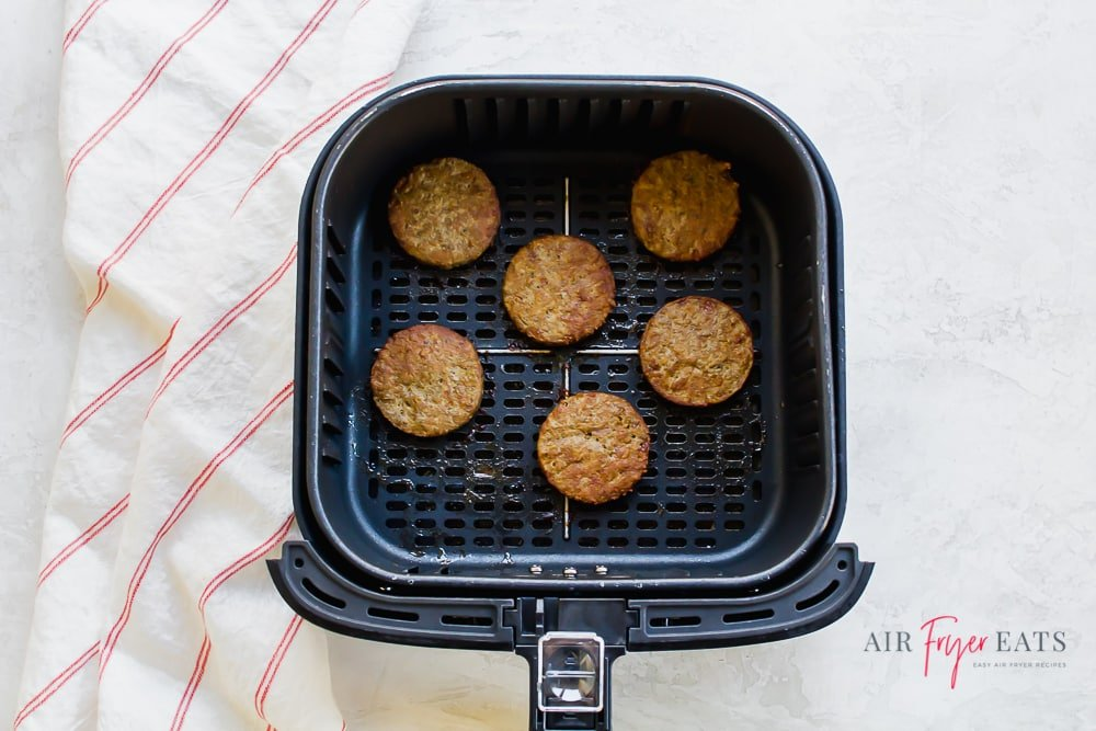 square air fryer basket with 6 cooked,round sausage patties