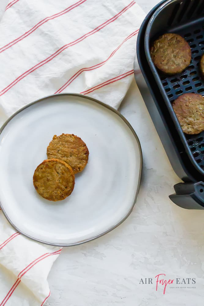 two sausage patties on a white plate next to a black air fryer basket full of sausage.