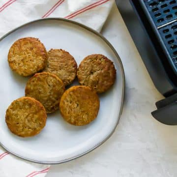 A white plate with 6 sausage patties