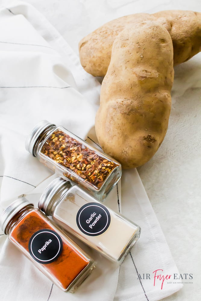 Two russet potatoes, a jar of red pepper flakes, a jar of garlic powder, and a jar of paprika, lying on a counter.