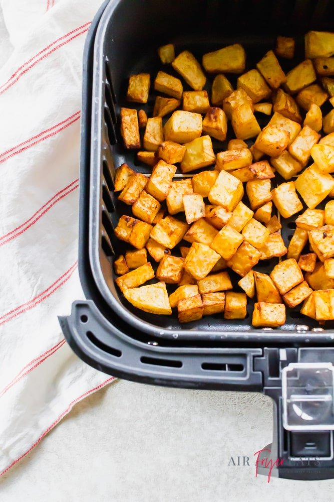 roasted cubed potatoes in an air fryer basket.