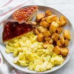 breakfast plate with potatoes, eggs, toast.
