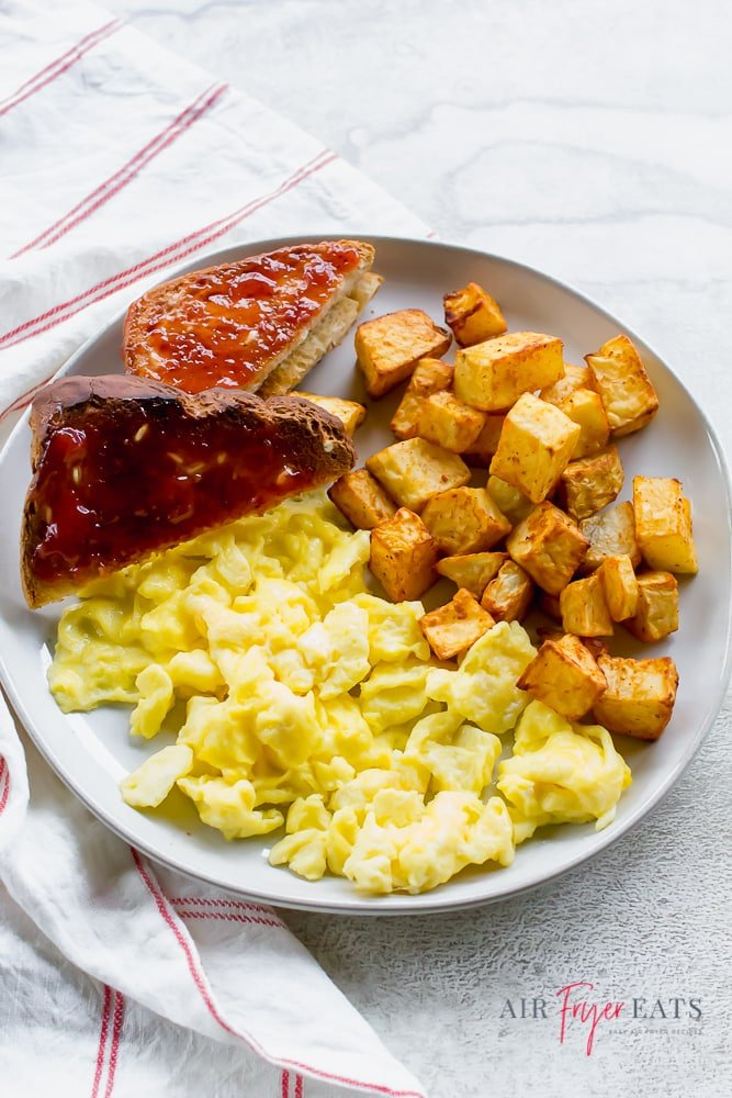 Breakfast plate that includes toast with jam, scrambled eggs, and cubed breakfast potatoes.