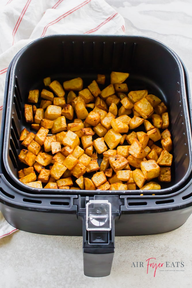 Top down view of cooked breakfast potatoes in the air fryer.