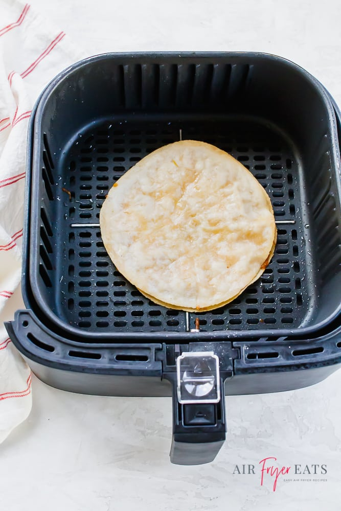 An air fryer basket with a cooked quesadilla inside.
