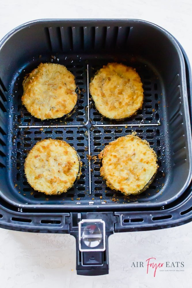 4 breaded eggplant slices in a square air fryer basket