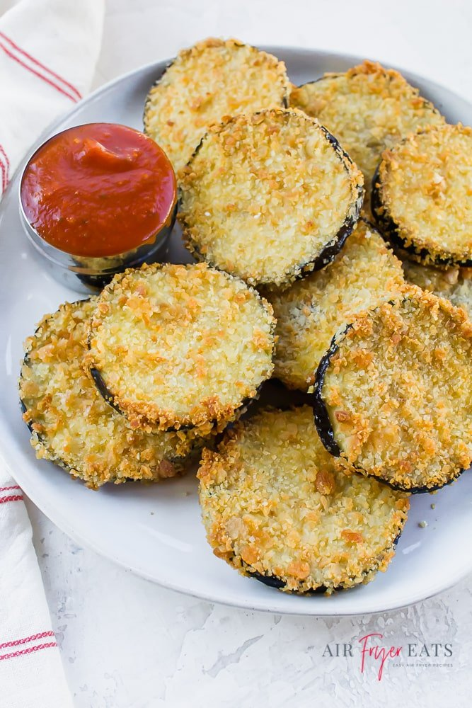 crispy eggplant rounds on a white plate with a side of marinara sauce.