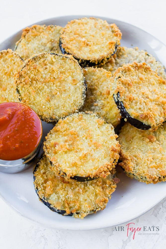 a white plate of crispy eggplant slices with a side of marinara sauce.