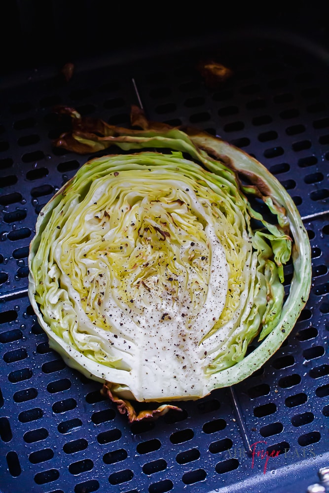 closeup view of a round cabbage slice in an air fryer basket.