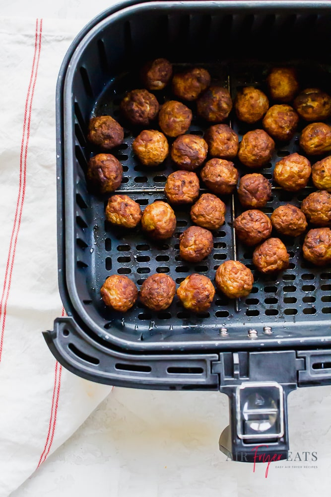 a square air fryer basket full of cooked meatballs.