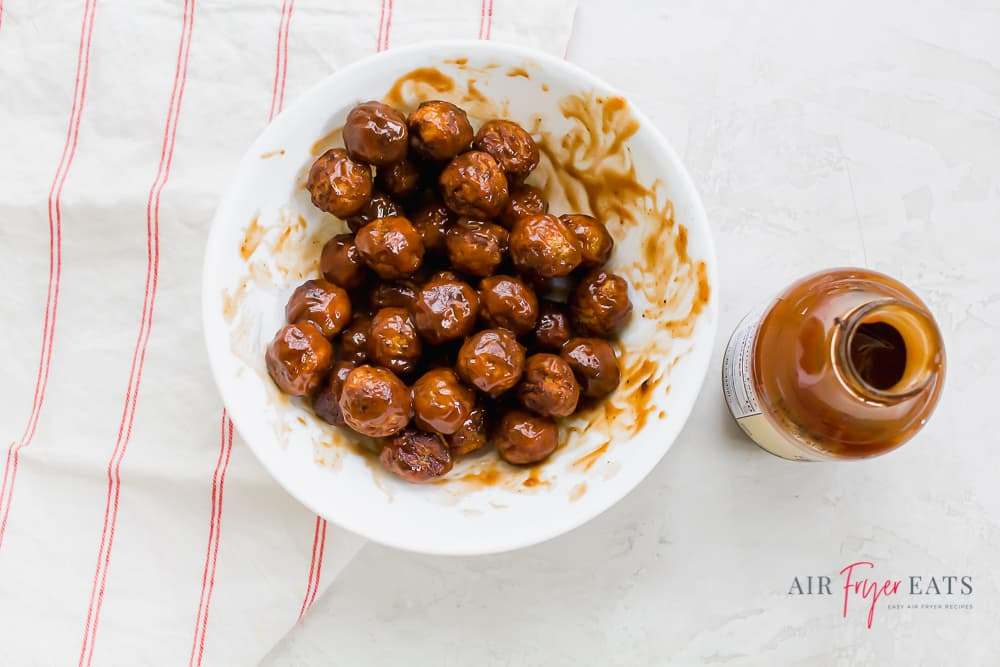 a bowl of bbq meatballs next to an open bottle of bbq sauce on a counter with a red striped towel.