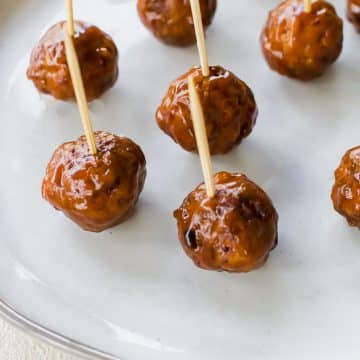 bbq meatballs with toothpicks on a white plate.