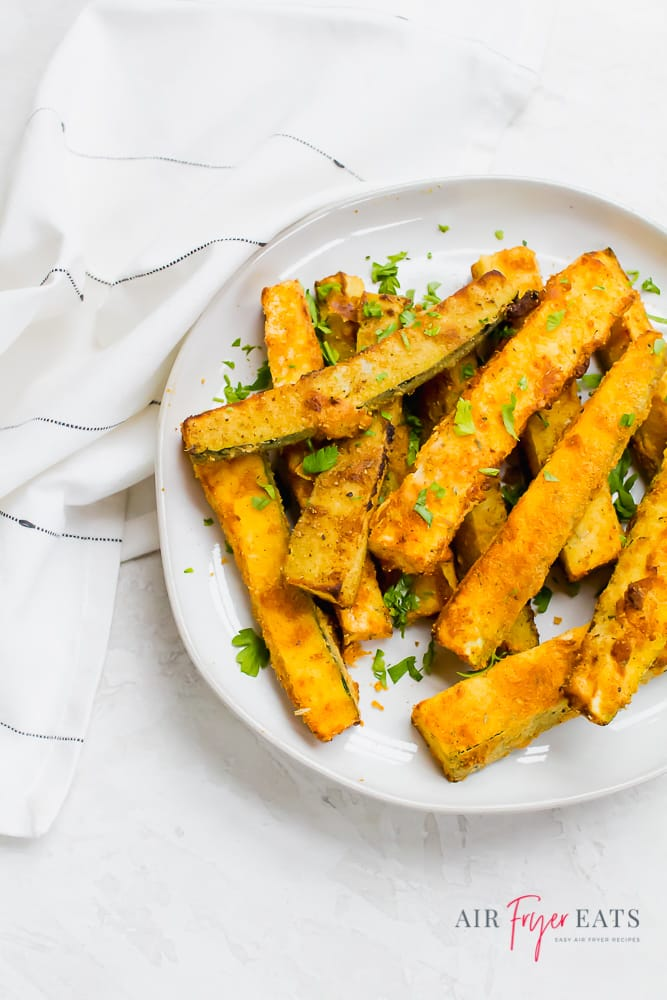 a white round plate of zucchini fries garnished with herbs.