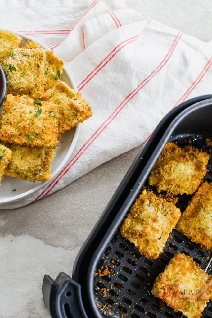 a white plate topped with fried ravioli next to an air fryer basket filled with fried ravioli.