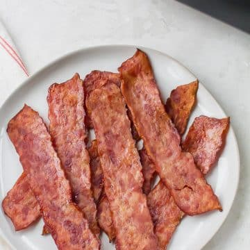a plate of cooked turkey bacon next to an air fryer.