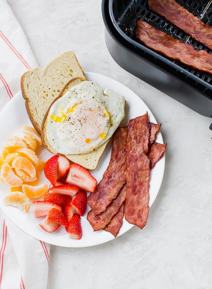 a plate of eggs, bacon, toast and fruit