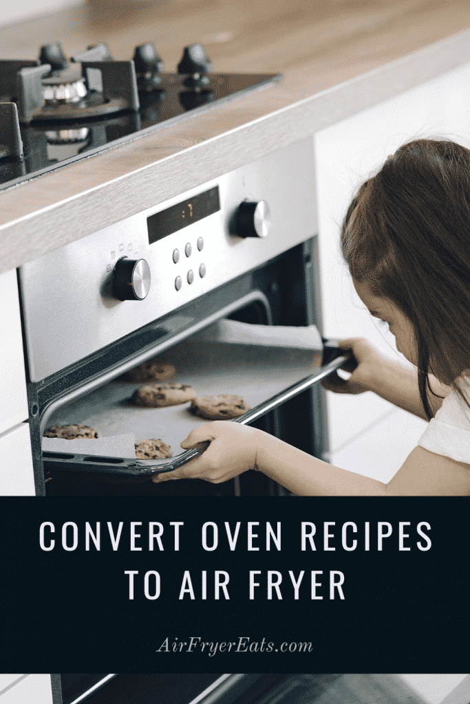 picture of a little girl putting a cookie sheet with cookies into the oven. Text overlay saying convert over recipes to air fryer