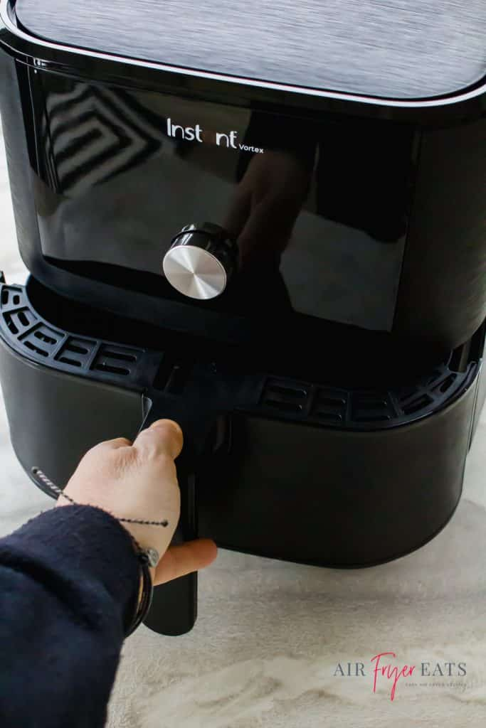 instant vortex air fryer with hand on basket pulling it out