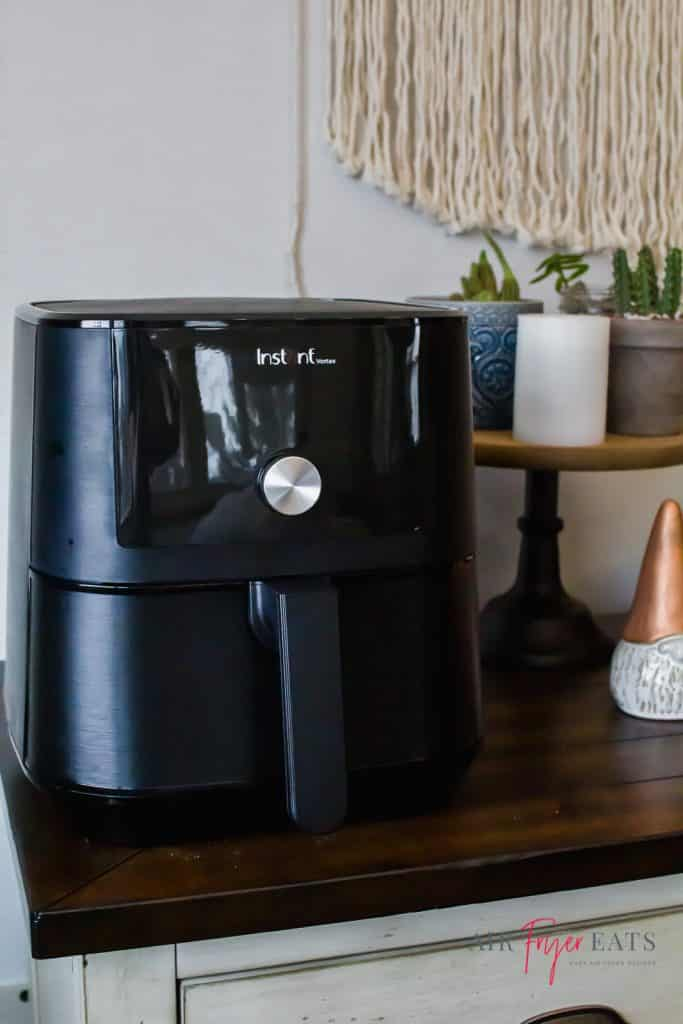 instant vortex black air fryer sitting on a buffet with a wooden top. a ghome with a copper hat sits to the right. Then a white candel with 3 catcus plants sits on a wooden top cake stand.