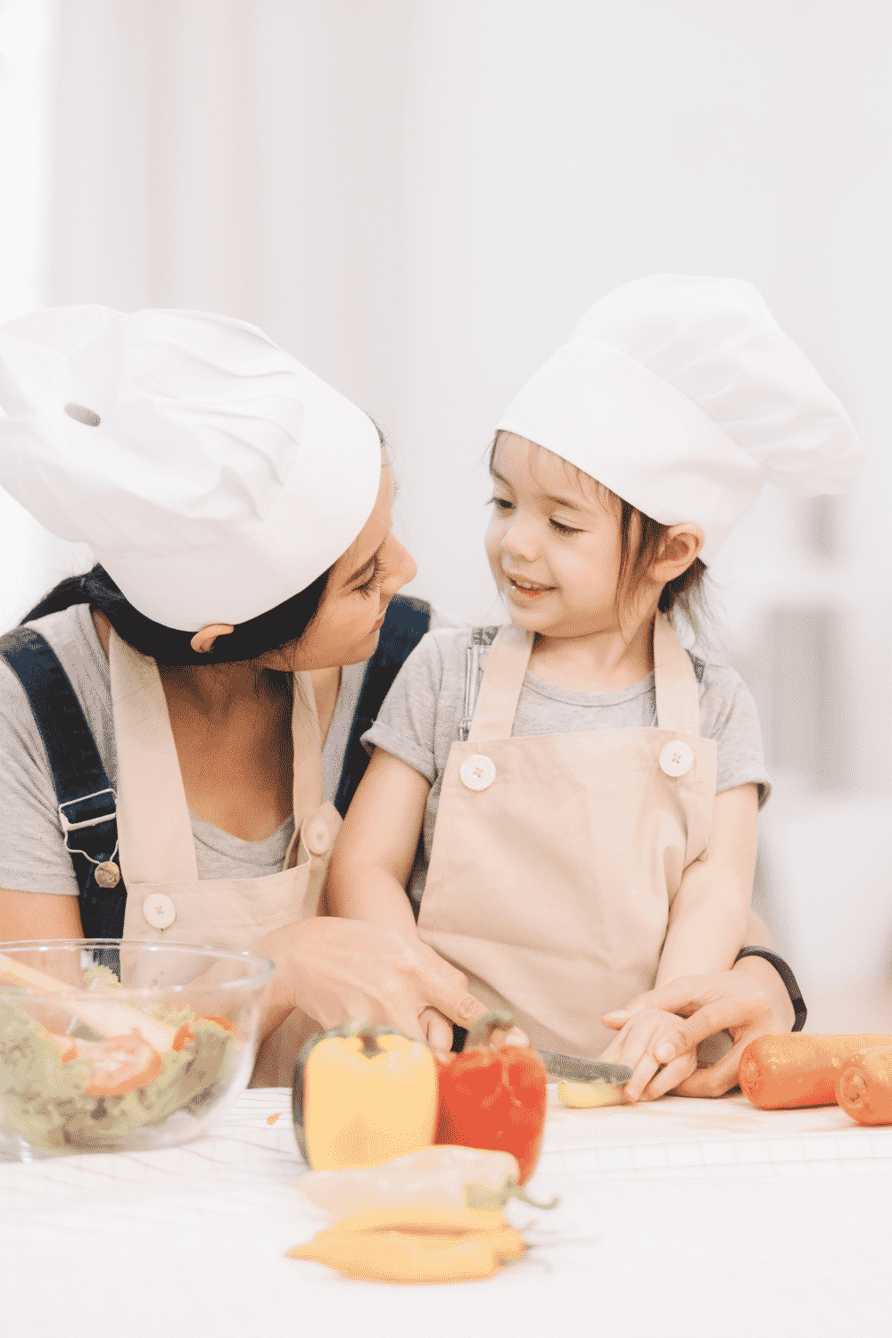 adult and kid cooking in the kitchen with white chef hats