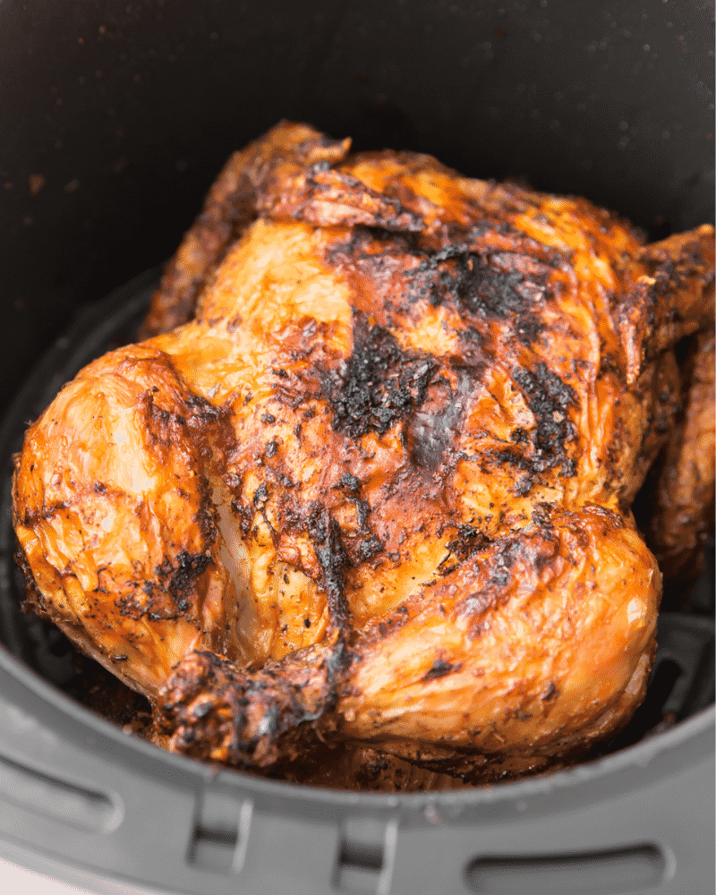 A whole chicken with crispy golden brown skin in an air fryer basket