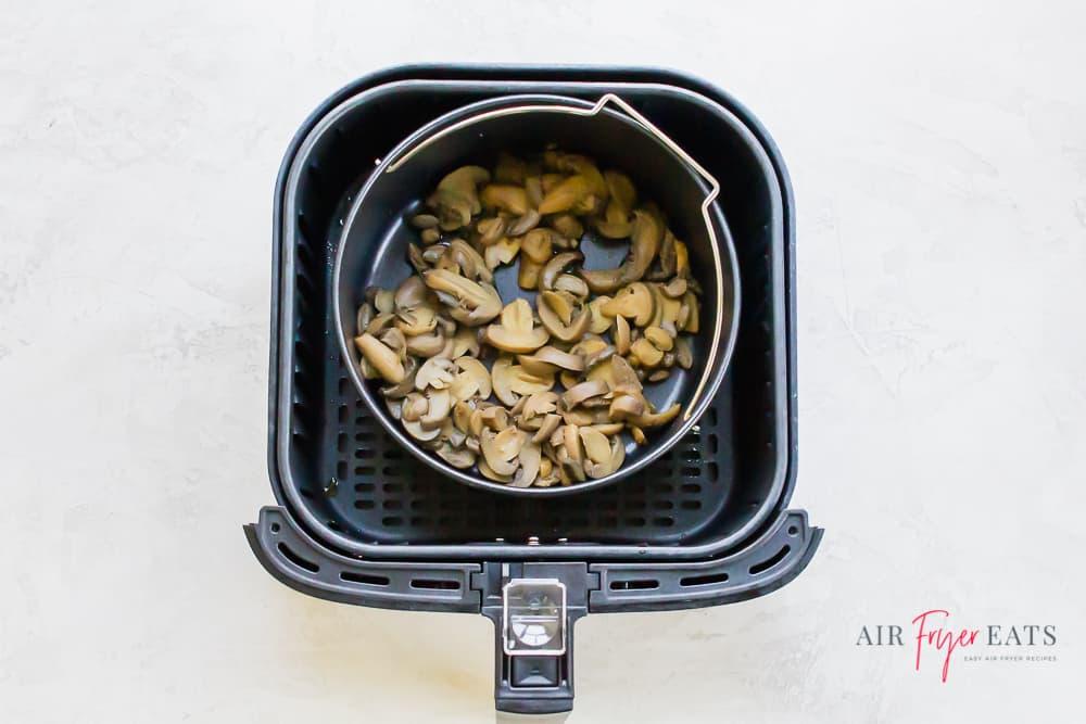 canned mushrooms in an air fryer pot inside of an air fryer basket