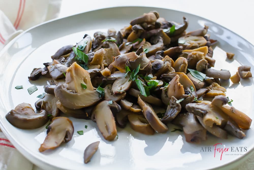 closeup view of mushrooms on a plate topped with herbs