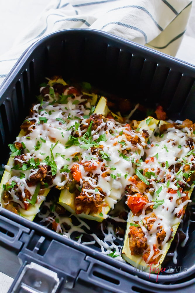 Stuffed zucchini topped with cheese in an air fryer basket