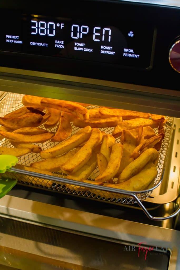 Cosori Air Fryer Toaster oven (black) with door open and fries inside