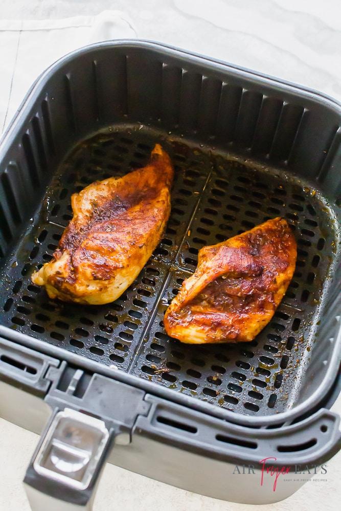 2 seasoned chicken breasts in an air fryer basket
