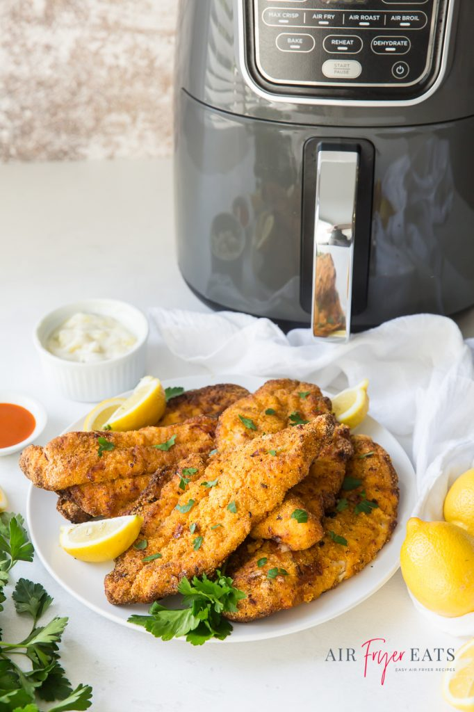 A plate of fried catfish with lemon wedges and fresh parsley in front of an air fryer