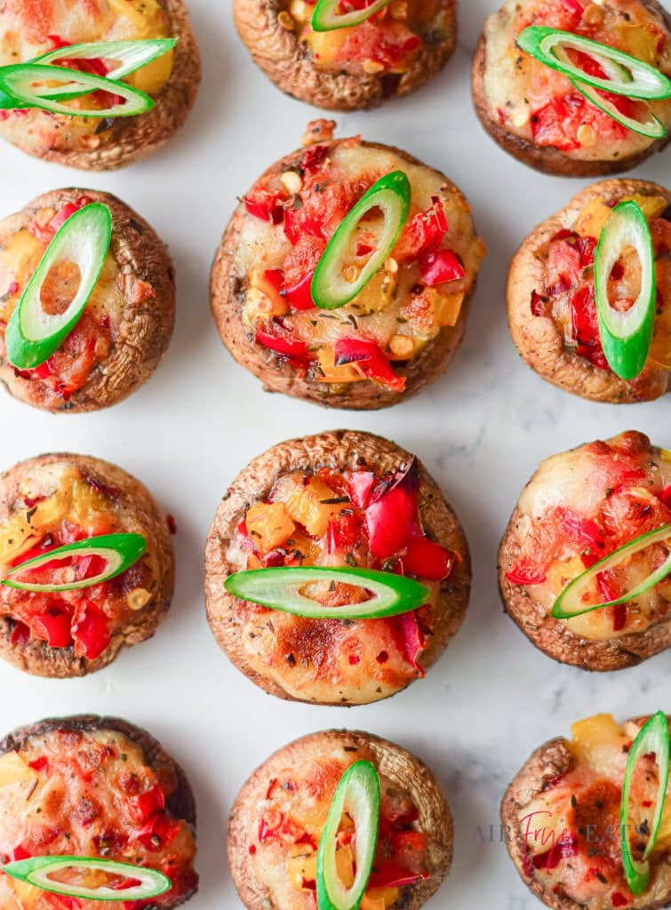 Rows of vegetarian stuffed mushrooms with mozzarella cheese, red bell peppers, and with green onions
