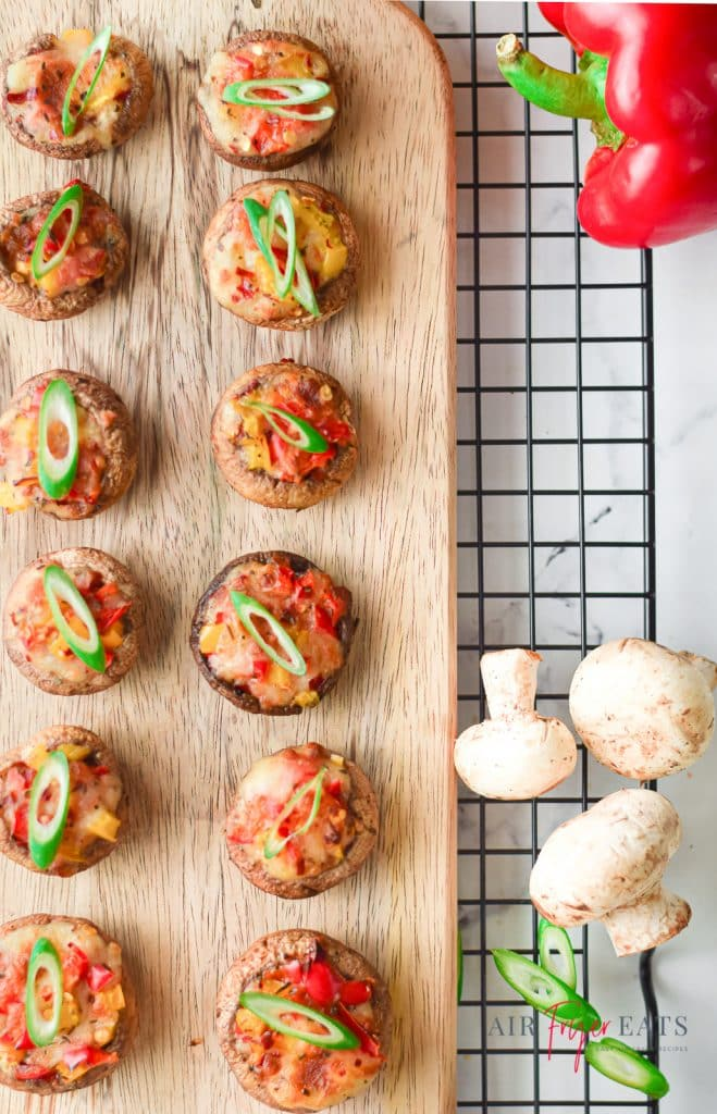 12 stuffed mushrooms on a wooden cutting board next to a red bell pepper and some mushrooms on a rack