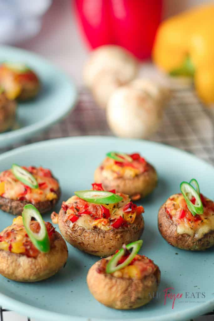 Turquoise plates of stuffed mushrooms with red bell peppers, green onions, and mozzarella cheese