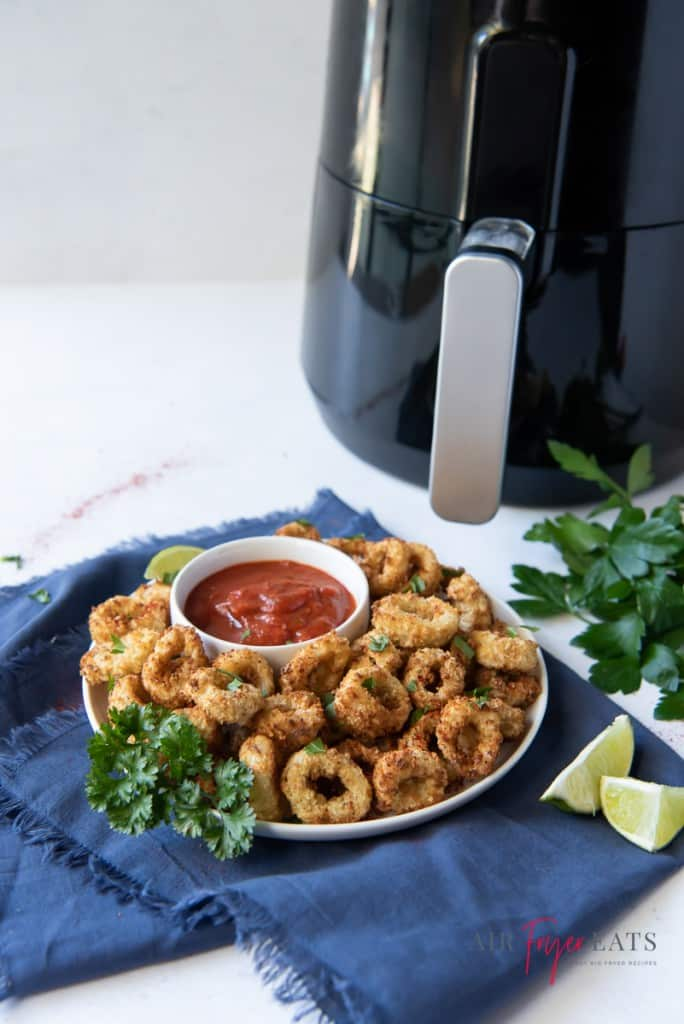 a round white plate of calamari rings and dipping sauce next to a black air fryer.