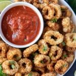 A platter of air fried calamari with a side of marinara sauce