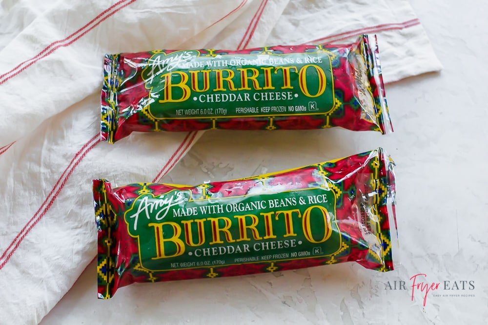 Two Amy's frozen burritos wrapped in green and red packaging on the counter.