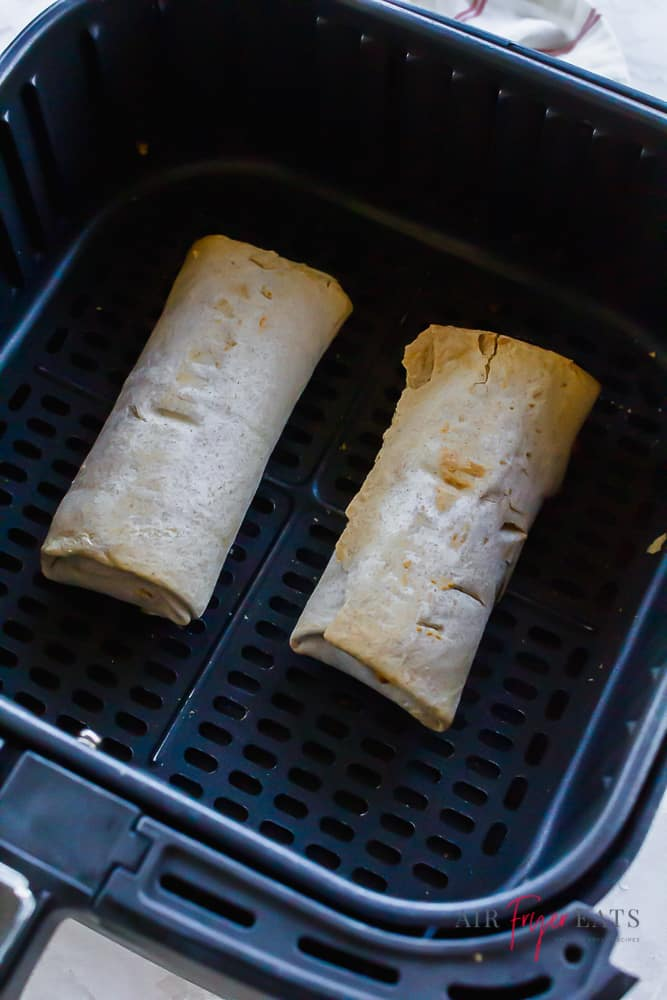 two frozen burritos in a square air fryer basket