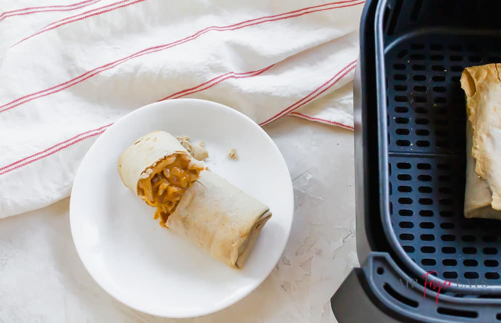 a white plate with a cut open burrito on it, next to a square air fryer basket.