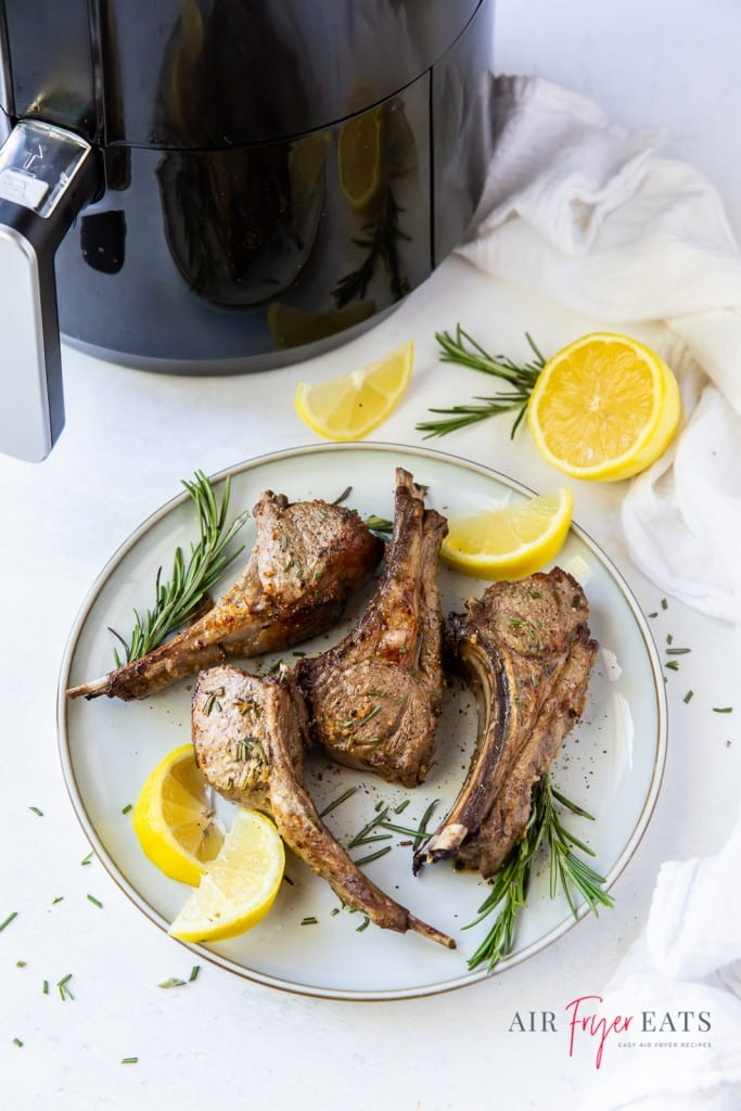 a white plate of lamb chops garnished with lemons and rosemary, next to an air fryer.