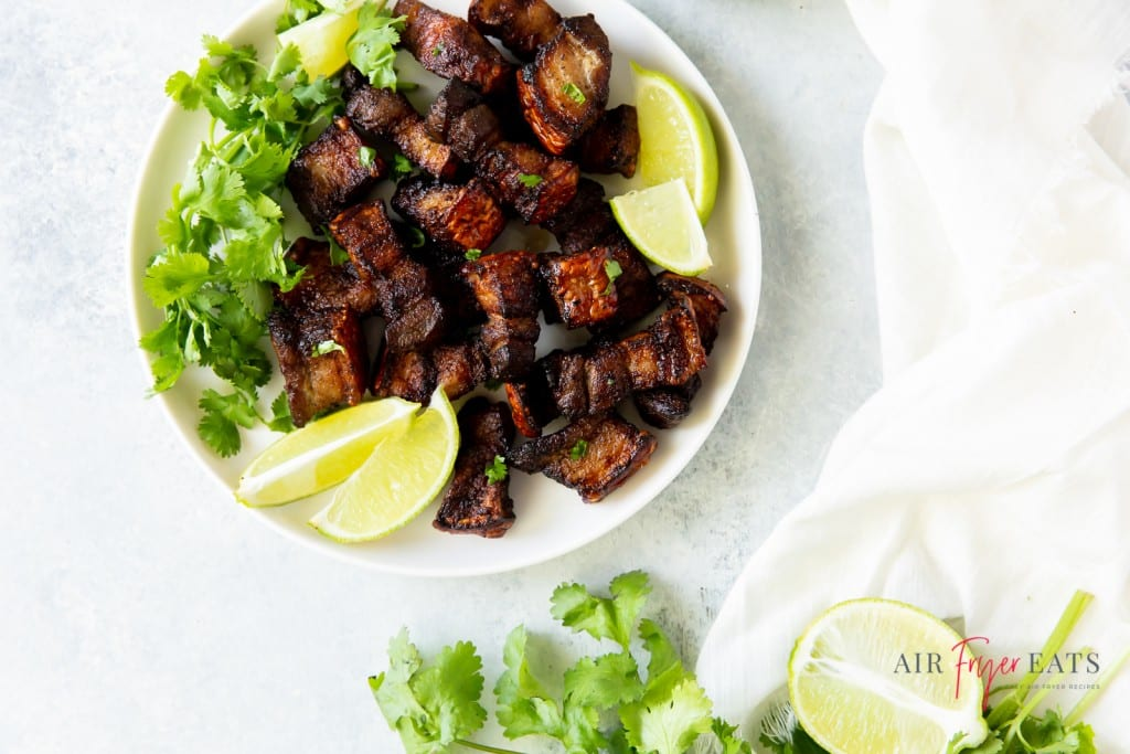 a white plate of crispy pork belly garnished with lime and cilantro