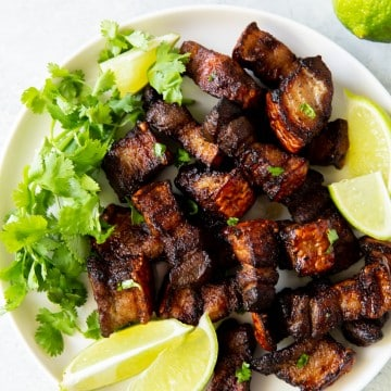 a white plate of pork belly pieces, lettuce, and lemon wedges